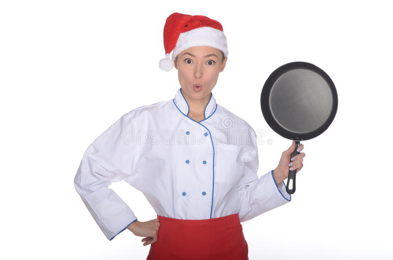 Cocinero asiático sorprendido con el sartén y el sombrero de la Navidad imagen de archivo libre de regalías