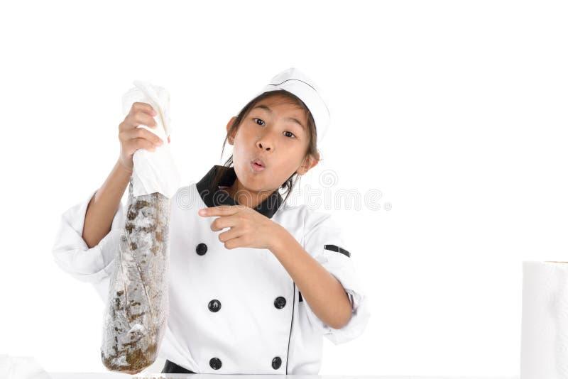 Cocinero asombrosamente en el uniforme que sostiene pescados de congelación grandes en blanco foto de archivo