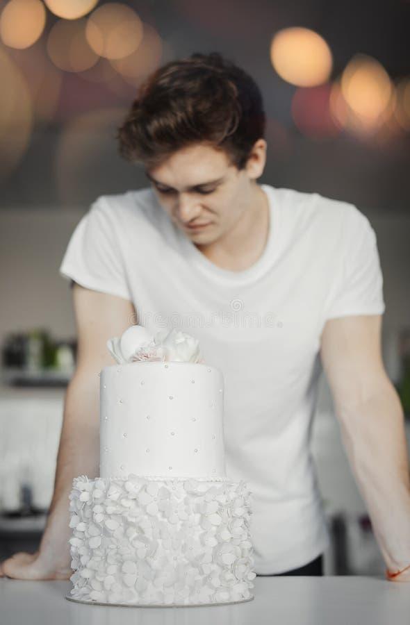 Cocinero atractivo joven que mira el pastel de bodas blanco imagen de archivo libre de regalías