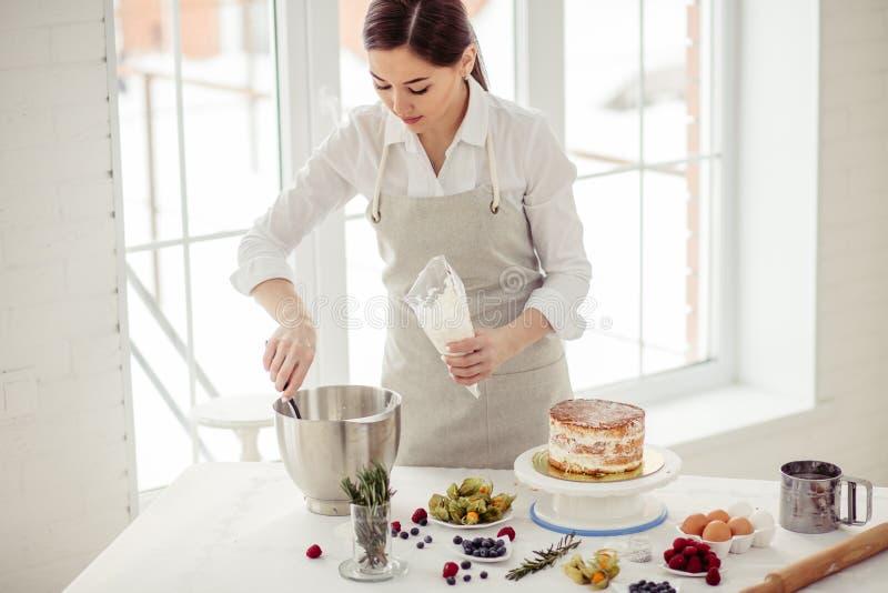 Cocinero atractivo joven que pone la crema en el bolso de los pasteles imagen de archivo