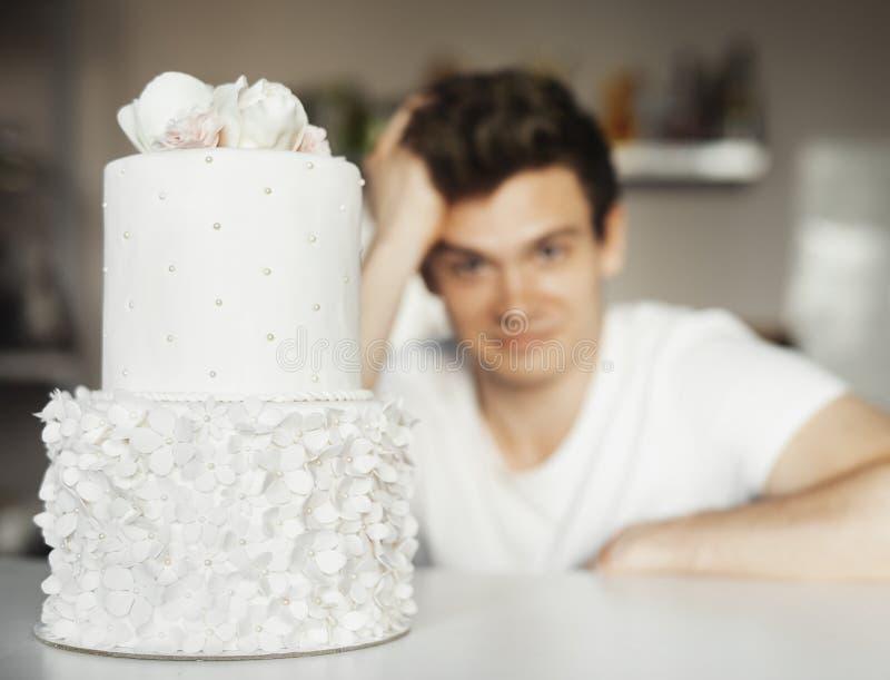 Cocinero atractivo joven que se sienta detrás del pastel de bodas hermoso blanco fotografía de archivo