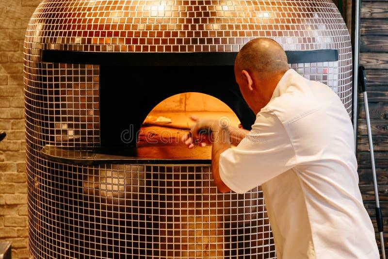 Cocinero Baking Caprese Bianca Pizza dentro del horno ardiente de madera de la pizza imagenes de archivo
