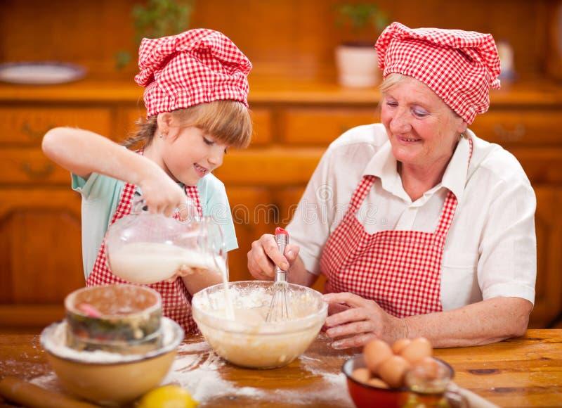 Cocinero Baking In Kitchen de la abuela y de la nieta imágenes de archivo libres de regalías