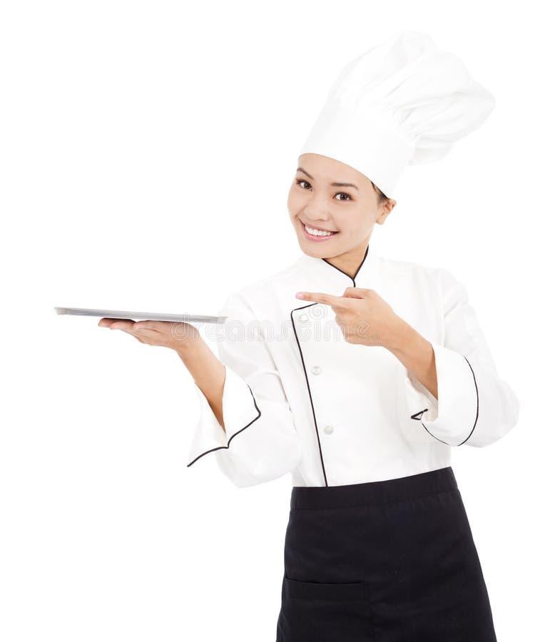 Cocinero bonito de la mujer del cocinero que celebra la bandeja y la mirada imagen de archivo