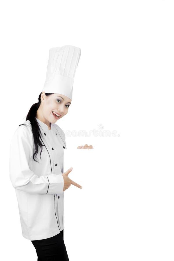 Cocinero bonito que muestra una cartelera en blanco fotos de archivo