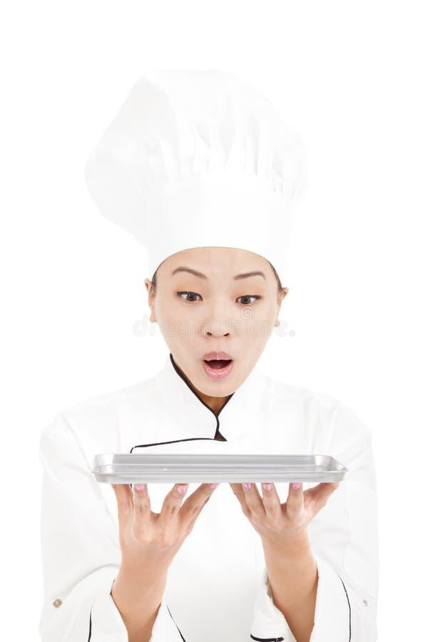 Cocinero bonito sorprendido de la mujer que mira la bandeja imagenes de archivo