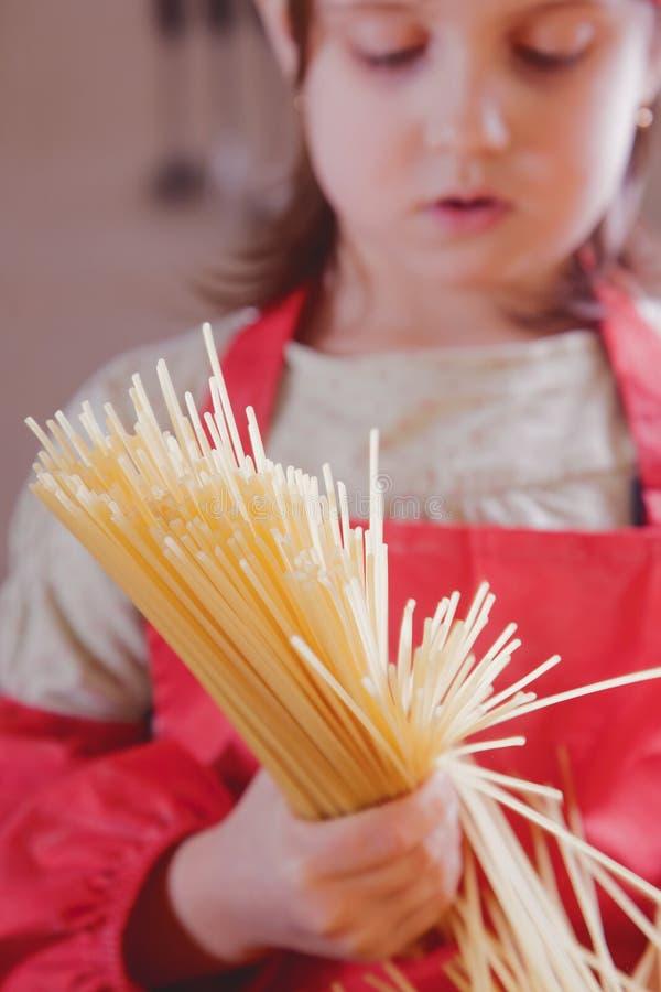Cocinero caucásico hermoso atractivo adorable encantador de la muchacha del niño que se divierte y praparing los fideos Proceso d fotografía de archivo