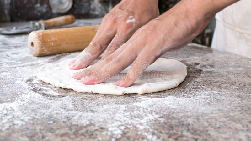 Cocinero cercano que hace la pizza, foco selectivo en frente fotografía de archivo