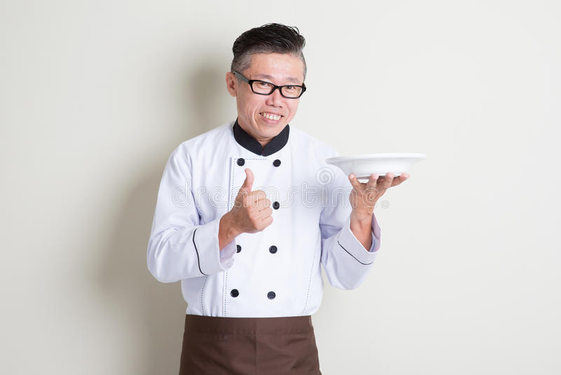 Cocinero chino asiático maduro que presenta el plato y el pulgar para arriba imagen de archivo