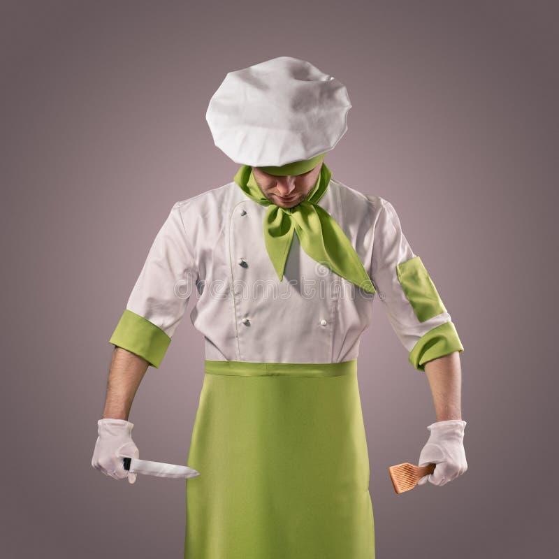 Cocinero con el cuchillo y la espátula de la cocina foto de archivo
