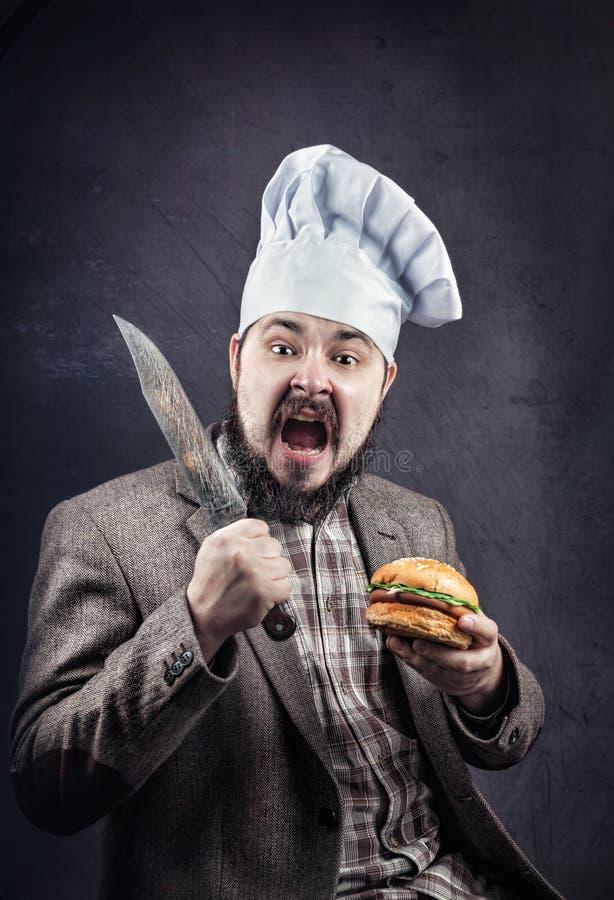 Cocinero con la hamburguesa y el cuchillo fotos de archivo
