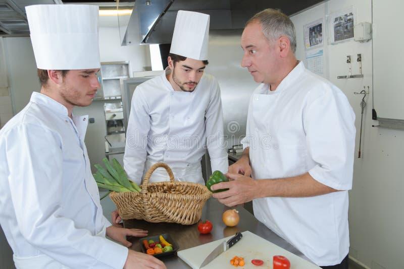 Cocinero con los aprendices que enseñan sobre verduras imagenes de archivo