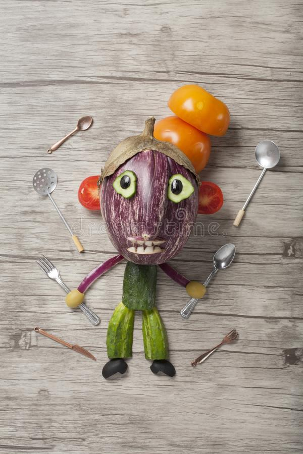 Cocinero creado de verduras con las herramientas de la cocina alrededor de él fotografía de archivo