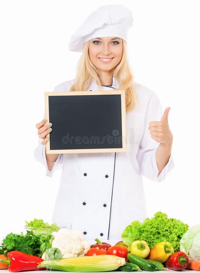 Cocinero de la mujer con la pequeña pizarra imagen de archivo libre de regalías