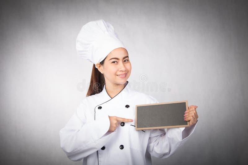 Cocinero de la mujer joven que lleva a cabo al tablero negro fotografía de archivo