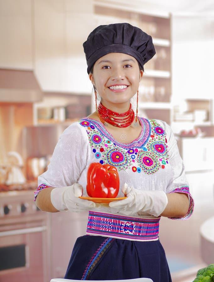 Cocinero de la mujer joven que lleva la blusa andina tradicional, sombrero de cocinar negro, soportando el pimiento rojo para la  fotografía de archivo
