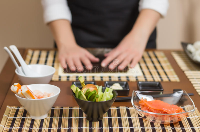 Cocinero de la mujer listo para preparar los rollos de sushi japoneses imagenes de archivo