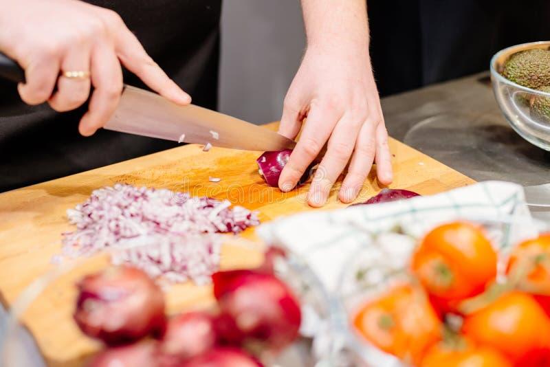 Cocinero de la mujer que corta la cebolla roja foto de archivo libre de regalías
