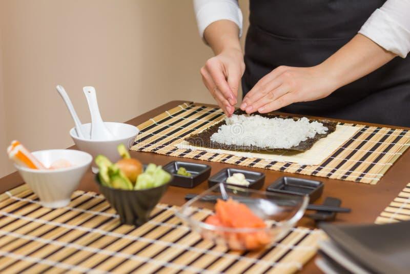 Cocinero de la mujer que llena los rollos de sushi japoneses de arroz fotos de archivo