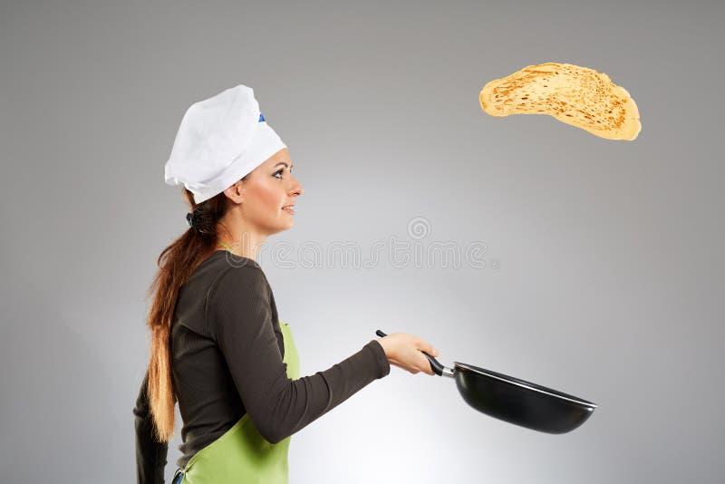 Cocinero de la mujer que mueve de un tirón la crepe foto de archivo