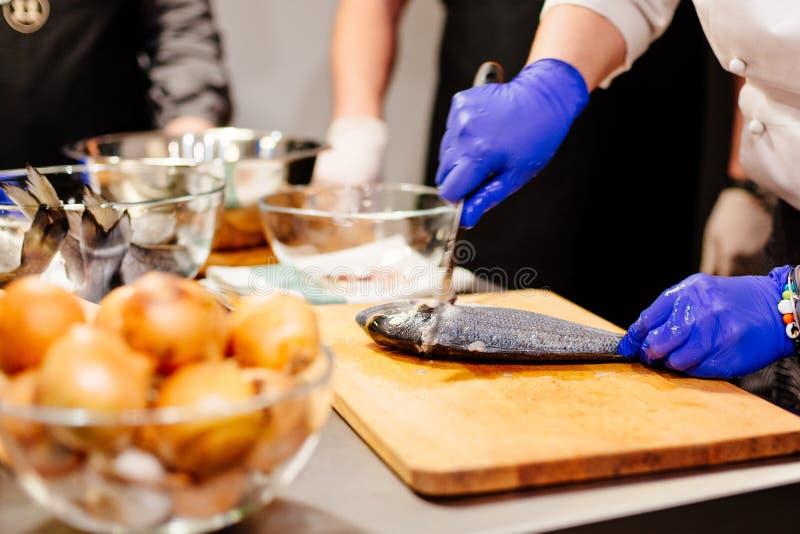 Cocinero de la mujer que prepara y que limpia pescados crudos del dorada fotos de archivo