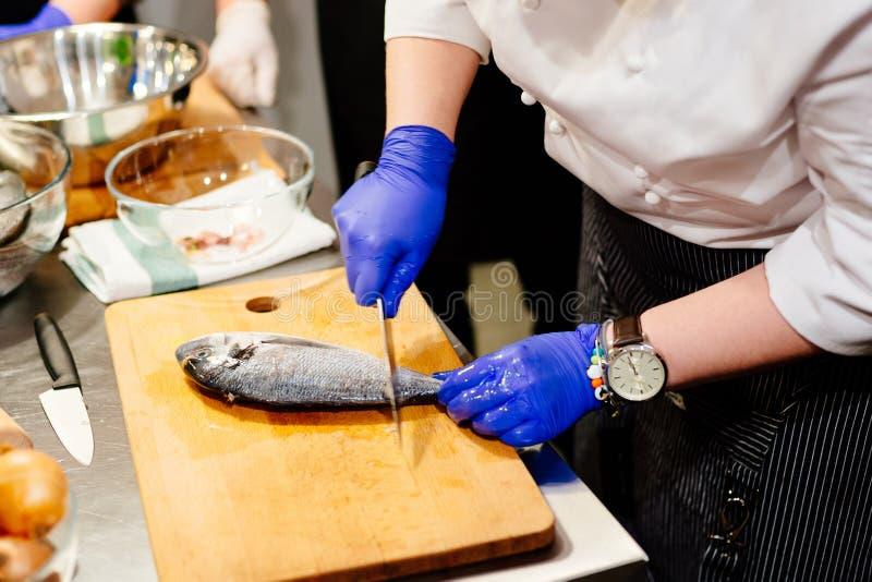 Cocinero de la mujer que prepara y que limpia pescados crudos del dorada fotografía de archivo libre de regalías