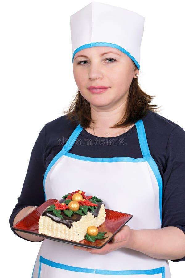 Cocinero de la mujer que sostiene una torta de la Navidad fotos de archivo