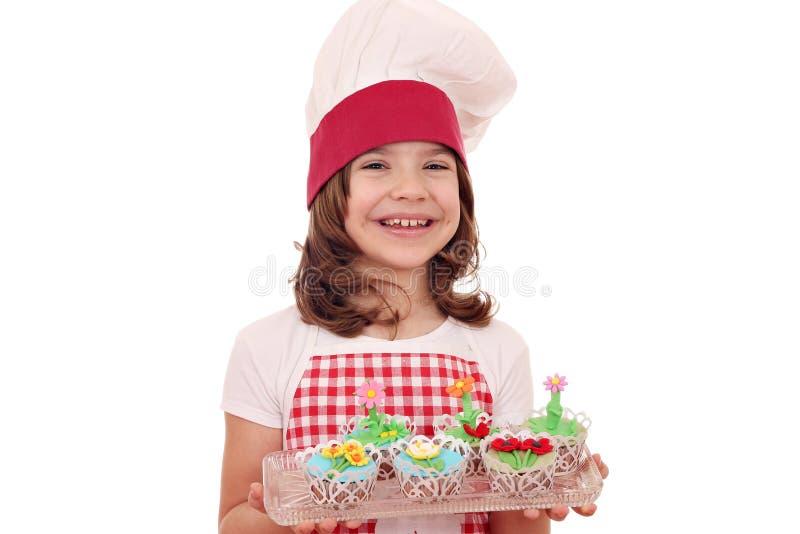 Cocinero de la niña con los molletes dulces adornados como flores de la primavera foto de archivo