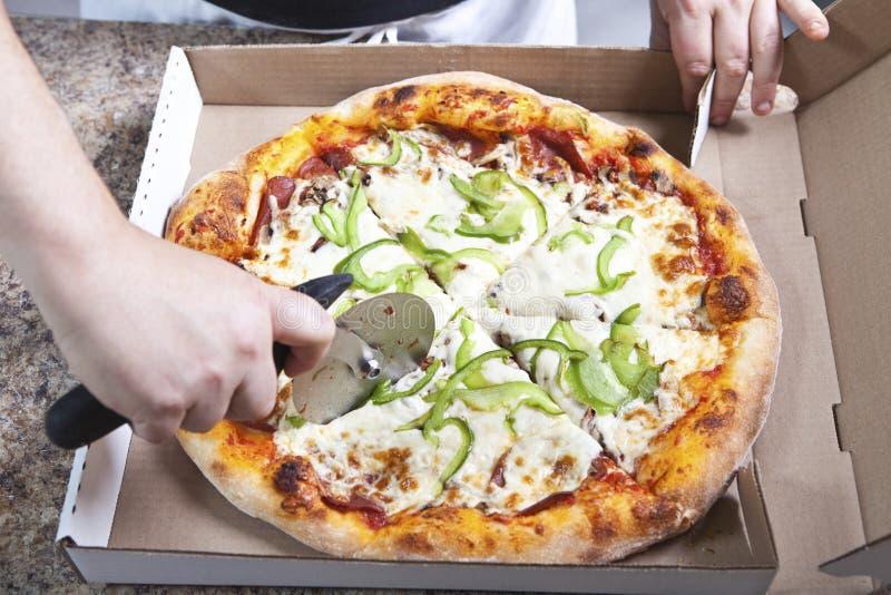 Cocinero de la pizza que corta la pizza fresca fotos de archivo libres de regalías