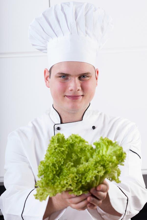 Cocinero de los jóvenes con lechuga imagenes de archivo