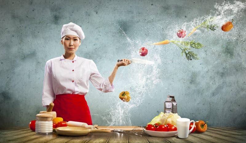 Cocinero de sexo femenino asiático con el cuchillo imagen de archivo libre de regalías