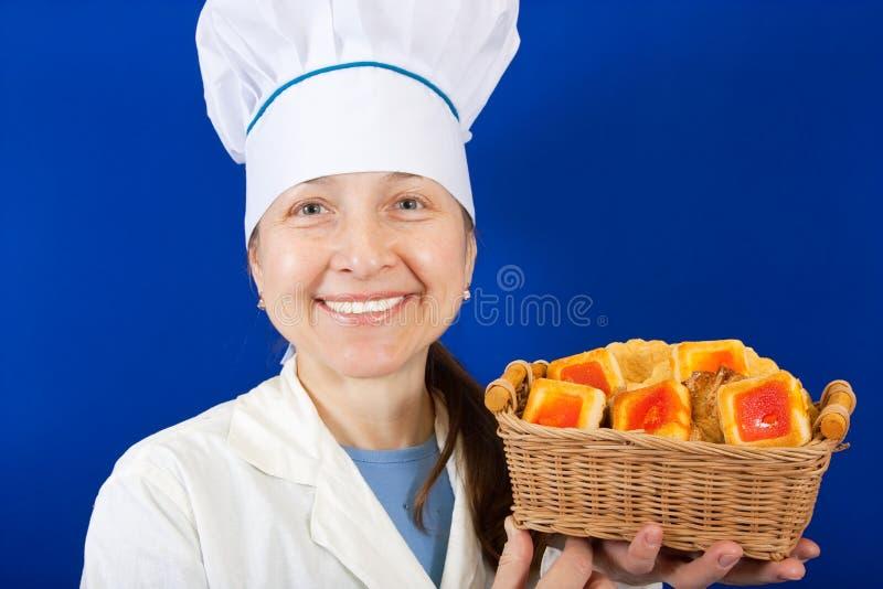 Cocinero de sexo femenino con la galleta sobre azul imagen de archivo libre de regalías