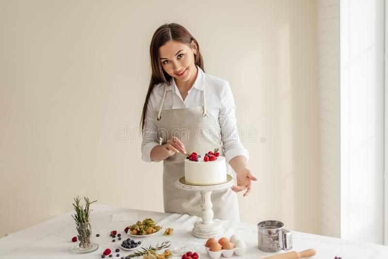 Cocinero de sexo femenino encantador sonriente que mira la cámara mientras que adorna la torta fotografía de archivo