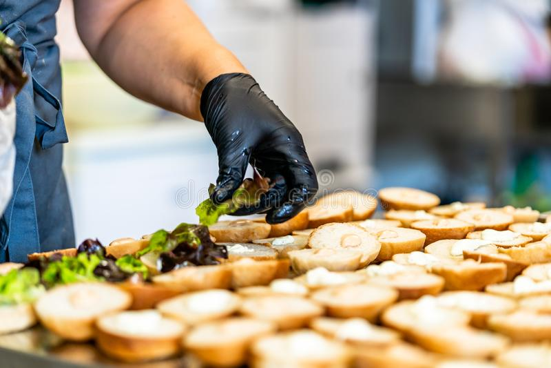 Cocinero de sexo femenino Putting Ingredients de hamburguesas en una extensión cortada del pan en una tabla foto de archivo