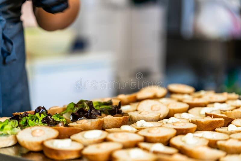 Cocinero de sexo femenino Putting Ingredients de hamburguesas en una extensión cortada del pan en una tabla fotos de archivo libres de regalías