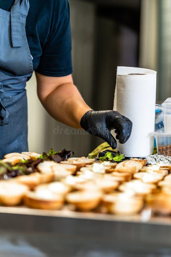 Cocinero de sexo femenino Putting Ingredients de hamburguesas en una extensión cortada del pan en una tabla imagen de archivo