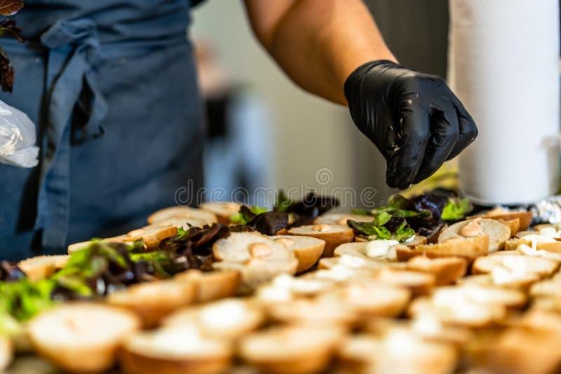 Cocinero de sexo femenino Putting Ingredients de hamburguesas en una extensión cortada del pan en una tabla imagenes de archivo