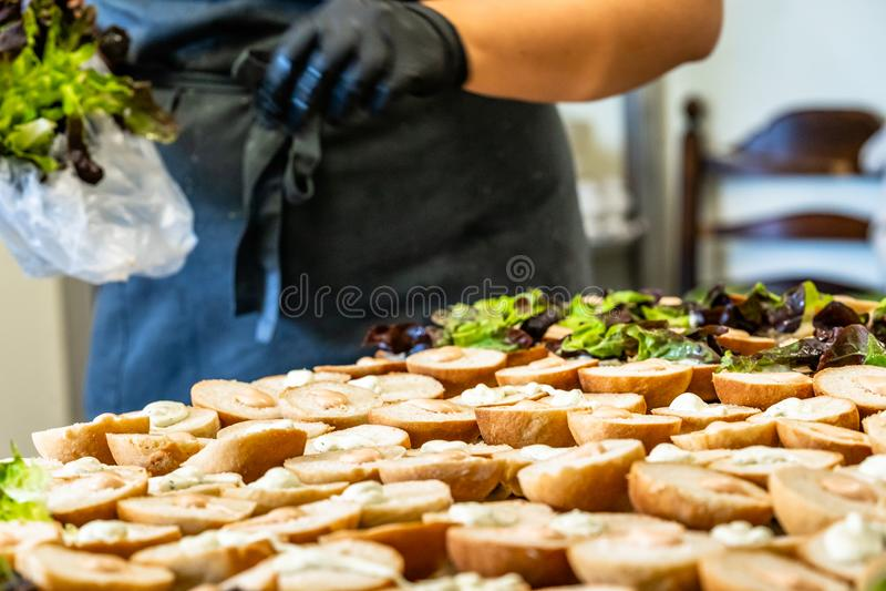 Cocinero de sexo femenino Putting Ingredients de hamburguesas en una extensión cortada del pan en una tabla fotografía de archivo libre de regalías
