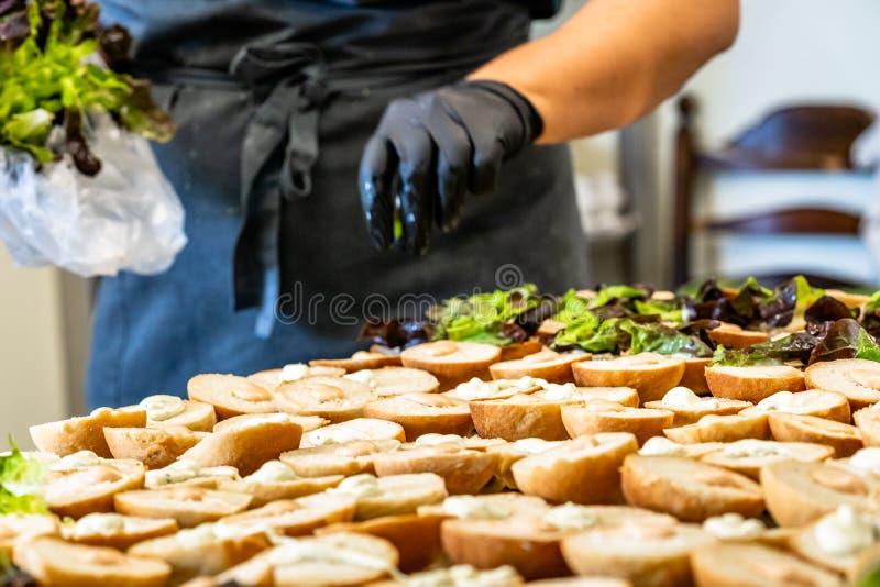 Cocinero de sexo femenino Putting Ingredients de hamburguesas en una extensión cortada del pan en una tabla foto de archivo libre de regalías