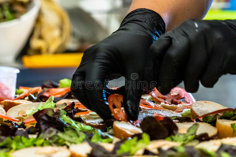 Cocinero de sexo femenino Putting Ingredients de hamburguesas en una extensión cortada del pan en una tabla fotos de archivo
