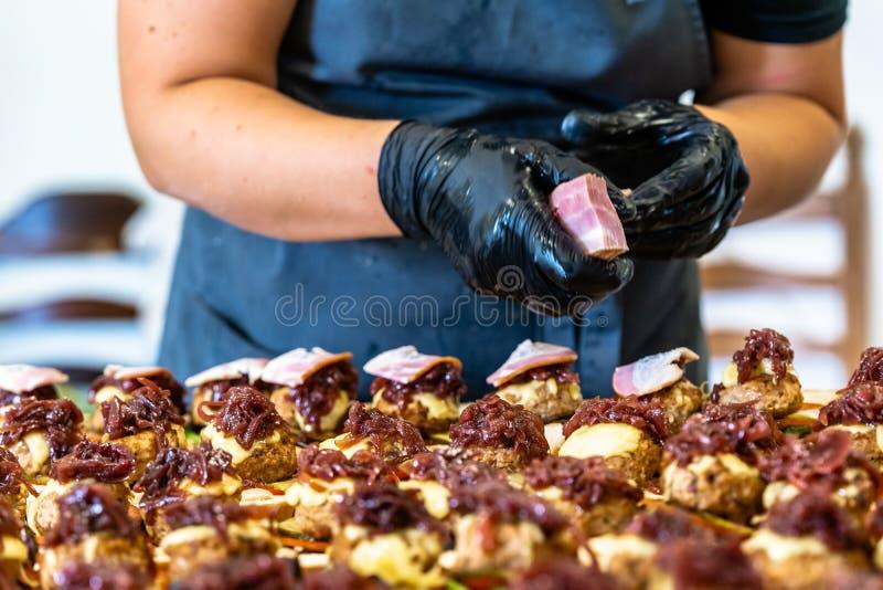 Cocinero de sexo femenino Putting Ingredients de hamburguesas en una extensión cortada del pan en una tabla en guantes negros foto de archivo libre de regalías