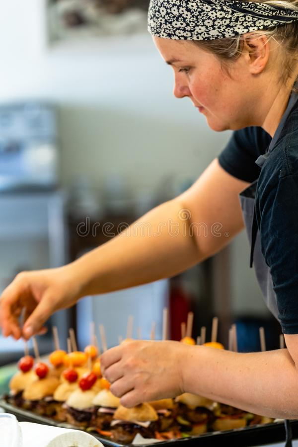 Cocinero de sexo femenino Putting Ingredients de hamburguesas en una extensión cortada del pan en una tabla en guantes negros fotos de archivo libres de regalías