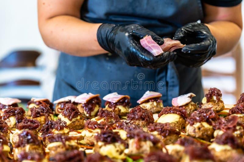 Cocinero de sexo femenino Putting Ingredients de hamburguesas en una extensión cortada del pan en una tabla en guantes negros imágenes de archivo libres de regalías