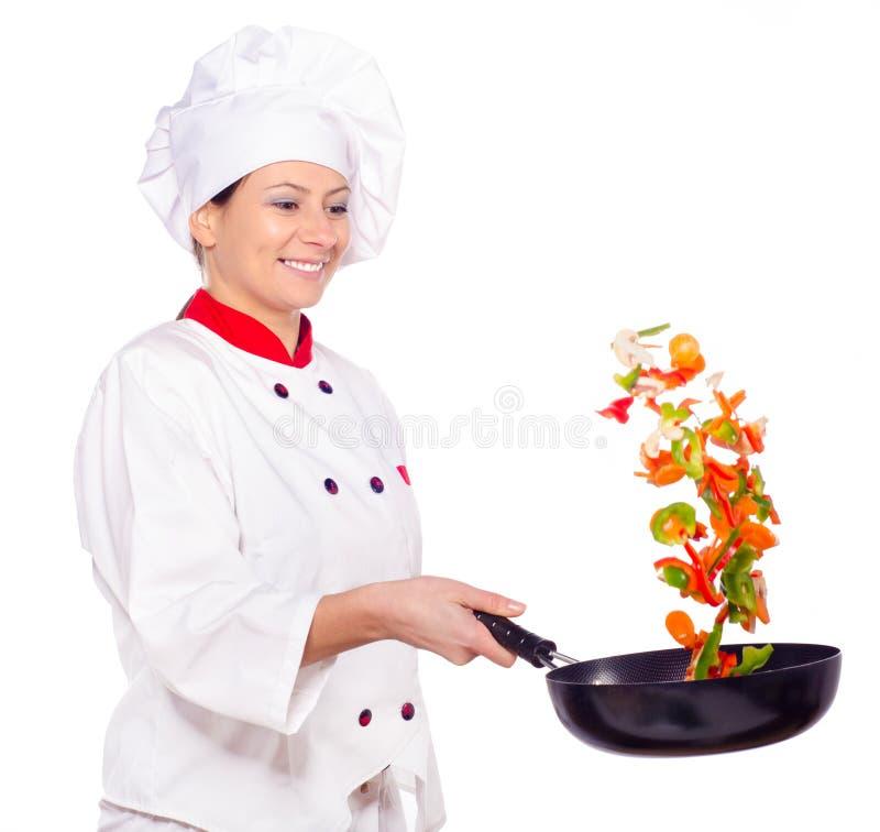 Cocinero de sexo femenino que fríe verduras en wok fotos de archivo