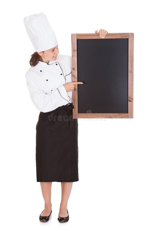 Cocinero de sexo femenino que lleva a cabo el tablero en blanco del menú imágenes de archivo libres de regalías