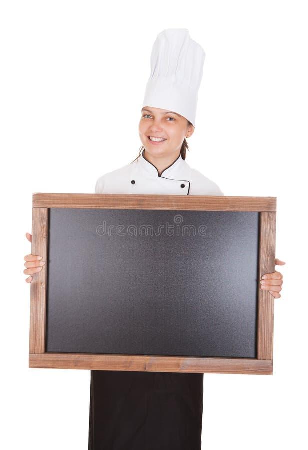 Cocinero de sexo femenino que lleva a cabo el tablero en blanco del menú fotografía de archivo libre de regalías
