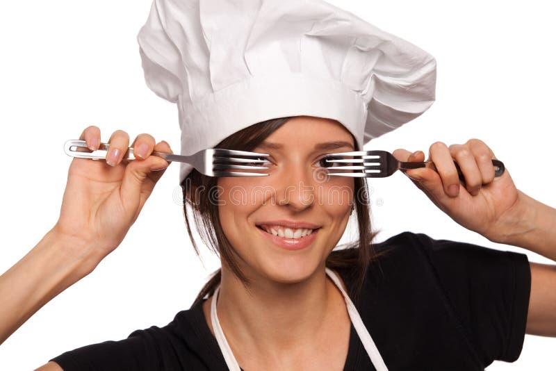 Cocinero de sexo femenino que mira a través de forkes imagenes de archivo