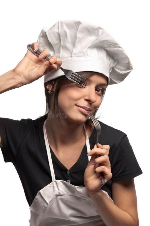 Cocinero de sexo femenino que mira a través de forkes imagen de archivo
