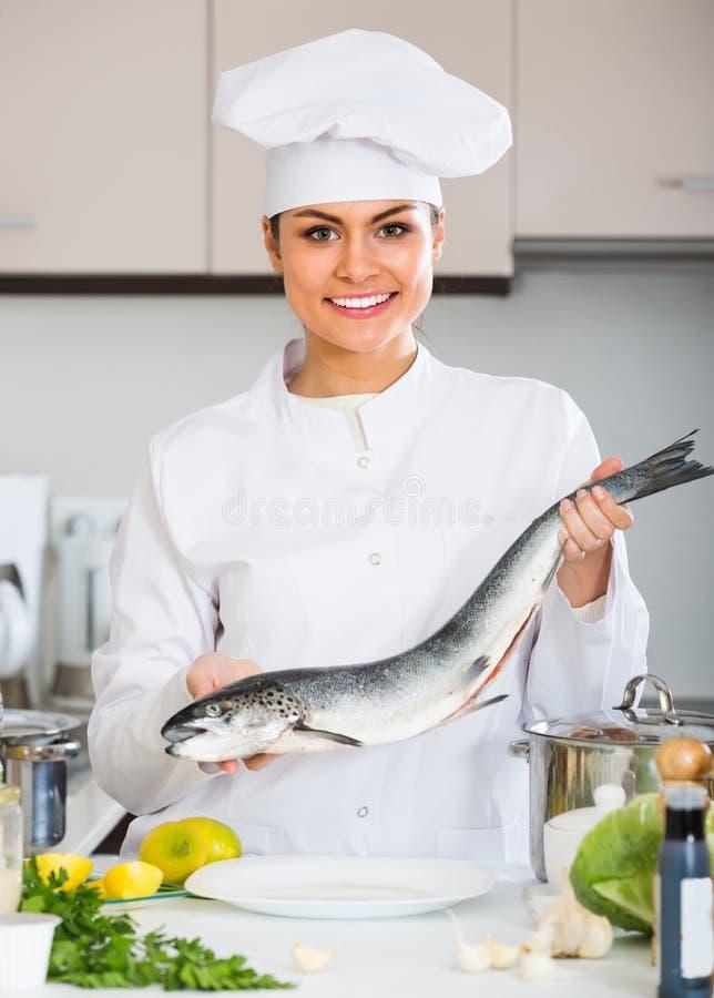 Cocinero de sexo femenino que prepara pescados grandes fotos de archivo libres de regalías
