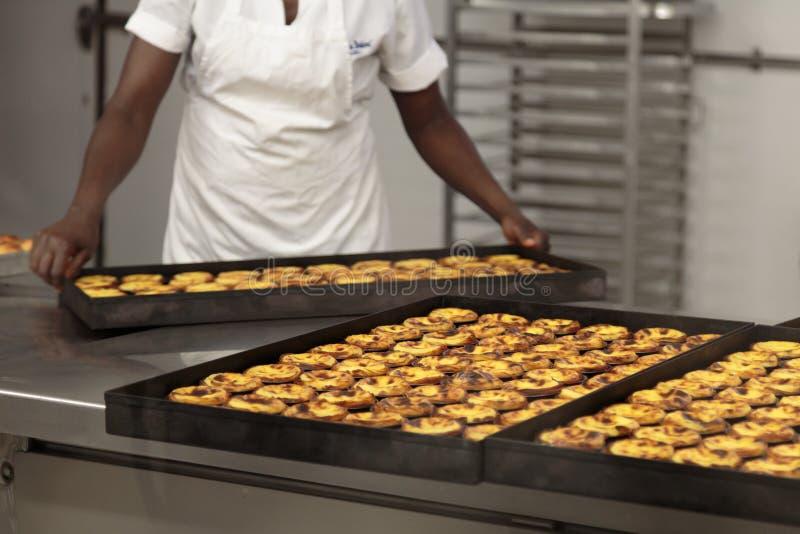 Cocinero de sexo femenino que prepara tartas portuguesas tradicionales del huevo en tienda de pasteles: Pastel de Nata foto de archivo